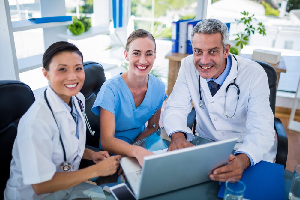 Doctors and nurse looking at laptop and smiling at camera in medical office